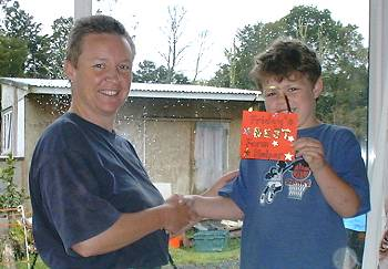 "Sebastian receiving the ""Friday's BEST Farm Helper"" award from Ruth"