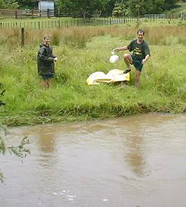 Neil with Graham, preparing to throw a bag of nappies over the flooded river