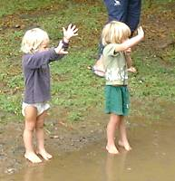 Patrick and Oliver waving to their Dad and Neil, across the flood