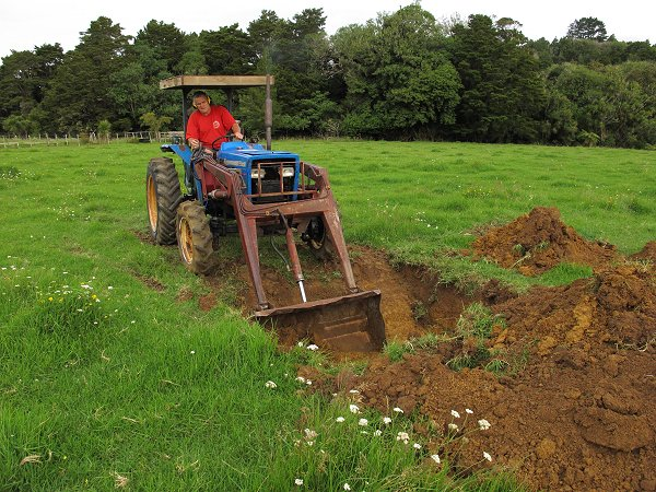 tractor digging a burial hole